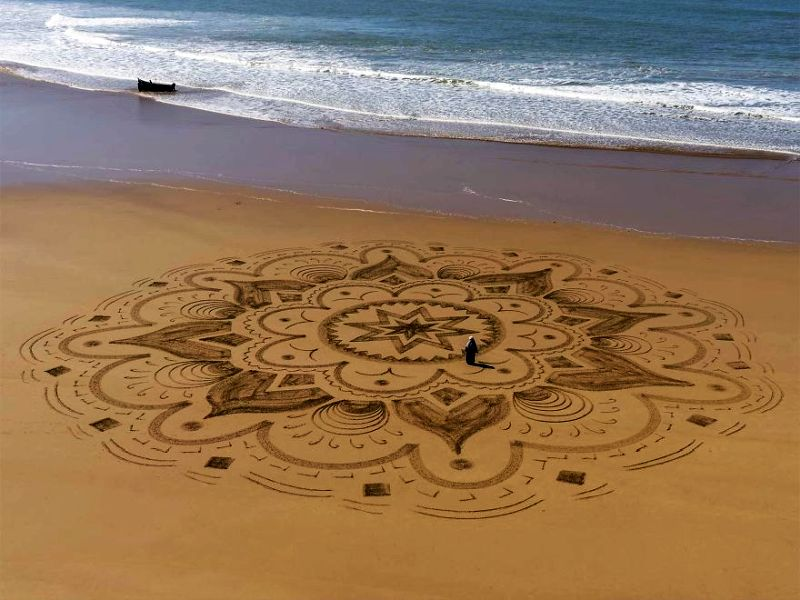 Artist creates huge mandalas on beach inspired by Arabic designs